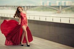 红色振翼的礼服的美丽的妇女 都市的背景 免版税库存图片