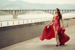 红色振翼的礼服的美丽的妇女 都市的背景 免版税库存照片
