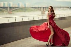 红色振翼的礼服的美丽的妇女 都市的背景 库存图片