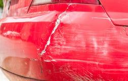 红色损坏了在崩溃事故的汽车与被抓的油漆并且消弱了后档金属身体 免版税图库摄影