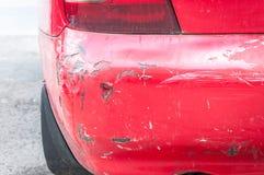 红色损坏了在崩溃事故的汽车与被抓的油漆并且消弱了后档金属身体 免版税库存照片