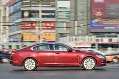 红色捷豹汽车XF轿车在繁忙的市中心,北京,中国 免版税库存照片