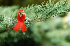 红色援助在绿色背景, HIV的丝带 库存图片