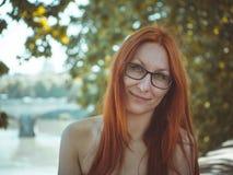 戴红色摆在罗马,意大利街道上的头发和眼镜的年轻美丽的俏丽的妇女  图库摄影