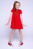 红色摆在象在白色背景的模型的礼服和运动鞋的美丽的矮小的红头发人女孩 库存图片