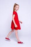 红色摆在象在白色背景的模型的礼服和运动鞋的美丽的矮小的红头发人女孩 免版税库存照片