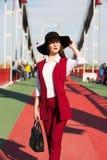 红色摆在a的长裤套装和黑帽会议的壮观的深色的夫人 库存图片