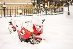 红色摩托车盖了雪 免版税库存图片