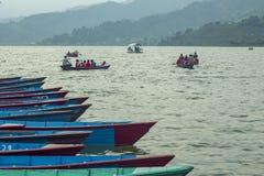 红色救生衣的游人在绿色山背景的一艘划艇在雾的 免版税库存图片