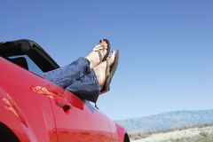 红色敞篷车的妇女有非常突出的腿的  免版税库存图片