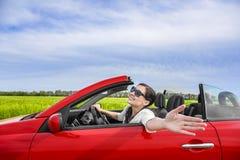 红色敞蓬车的妇女在与风力的一个领域 免版税库存照片