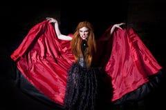 红色斗篷的可怕的吸血鬼妇女 免版税图库摄影