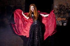红色斗篷的可怕的吸血鬼妇女 库存图片
