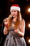 红色新年帽子的年轻白肤金发的可爱的妇女有话筒和闪烁发光物的 免版税图库摄影