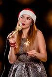 红色新年帽子的年轻白肤金发的可爱的妇女有话筒和闪烁发光物的 库存图片