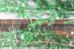 红色新年的锥体在冷杉分支围拢的一个木棕色架子说谎 免版税图库摄影