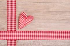 红色方格的心脏和丝带在木头 免版税图库摄影