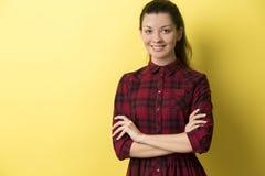 红色方格的礼服的女孩反对黄色背景 免版税库存照片