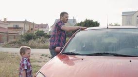 红色方格的衬衣的年轻爸爸洗涤他的汽车的挡风玻璃窗口和敞篷有他的小儿子慢动作的 股票视频
