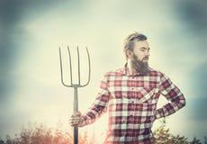 红色方格的衬衣的年轻有胡子的农夫有老干草叉天空自然backgrund的,被定调子 图库摄影
