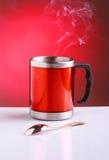红色旅行杯子用热茶和匙子 免版税图库摄影