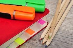 红色日志笔记本和色的铅笔,在桌木头的标志 库存照片