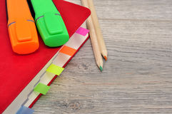 红色日志笔记本和色的铅笔,在桌木头的标志 库存图片