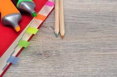 红色日志笔记本和色的铅笔,在桌木头的标志 免版税库存照片