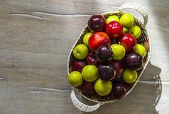 红色日本李子和樱桃在篮子,不同的颜色李子在篮子 免版税图库摄影