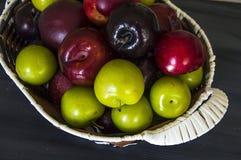 红色日本李子和樱桃在篮子 免版税库存图片