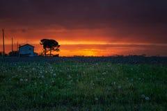 红色日落多云天空在北意大利 库存照片