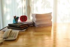 红色时钟和办公用品在书桌上在家庭办公室 库存照片