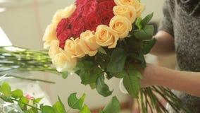 红色明亮的五颜六色的花束和桃子玫瑰,卖花人妇女会集花束 影视素材