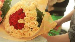 红色明亮的五颜六色的花束和桃子玫瑰,卖花人妇女会集花束 股票录像
