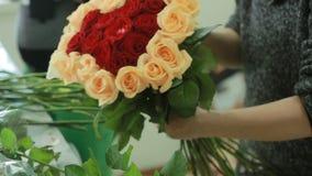 红色明亮的五颜六色的花束和桃子玫瑰,卖花人妇女会集花束 股票视频