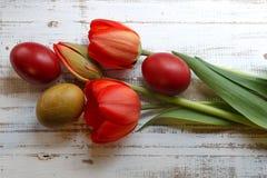 红色春天郁金香和手工制造五颜六色的被绘的复活节彩蛋花束反对土气木背景 免版税库存照片