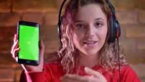 红色有冠乌鸦和耳机的年轻女性博客作者显示智能手机绿色显示到膝上型计算机里bricken墙壁 股票视频
