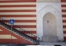 红色有楼梯的白色镶边墙壁和横渡标志和 库存图片