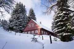 红色木客舱在一个冷淡的多雪的国家 图库摄影