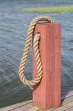 红色木小船系船柱和绳索 免版税库存图片