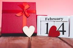 红色木心脏和礼物盒在木和桃红色背景 库存照片