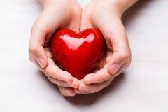 红色木心脏在儿童手上 库存图片