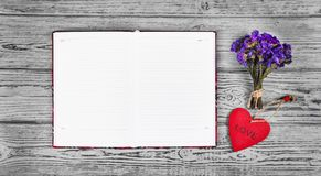 红色木心脏垂饰、一本开放日志与干净的页和干花 浪漫概念 背景和纹理 库存照片