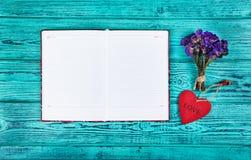红色木心脏垂饰、一本开放日志与干净的页和花 浪漫概念 背景和纹理 库存照片