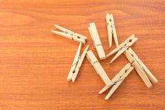 红色木表面上的混合木晒衣夹 免版税库存照片
