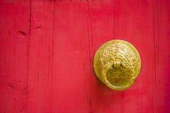 红色木门和中国寺庙或宫殿的金黄敲门人门背景和纹理的 库存照片