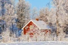 红色村庄在冬天森林里 免版税库存图片