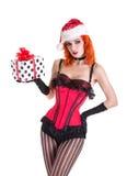 红色束腰和圣诞老人帽子的美丽的画报女孩,举行 免版税库存图片