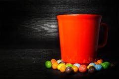 红色杯子五颜六色的糖果周围在黑木纹理backg的 库存照片