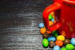 红色杯子五颜六色的糖果周围在黑木纹理backg的 库存图片